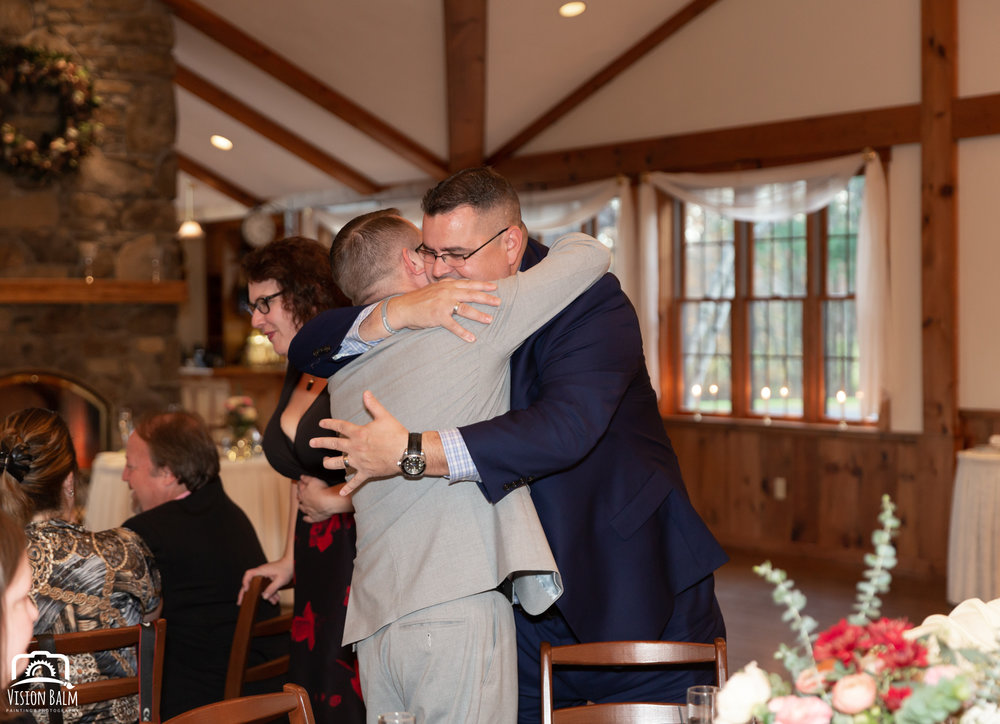 Wedding photo of groom hugging a guest in the venue of Zuka's Hilltop Barn by Vision Balm in Charleston, SC.