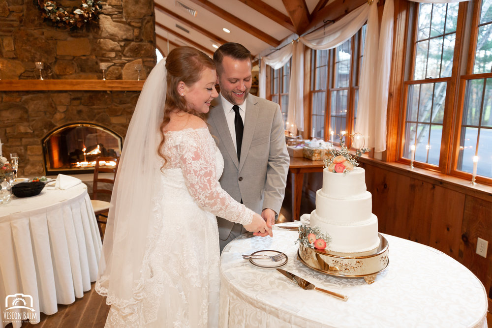 Wedding photo of groom and bride cutting a wedding cake in the venue of Zuka's Hilltop Barn by Vision Balm in Charleston, SC.