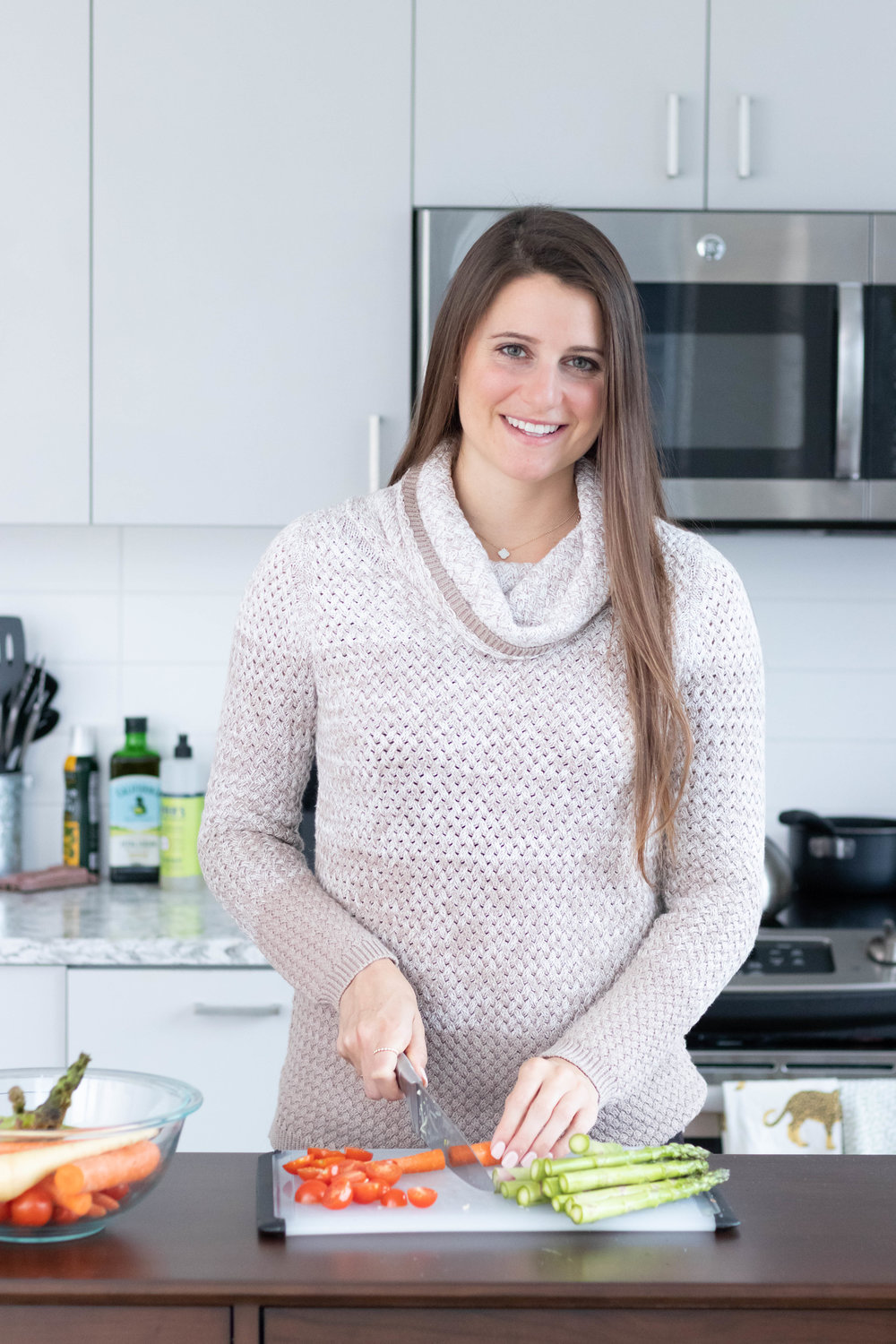 Lifestyle portrait photography of Erin Kenney from Nutrition Rewired registered dieititan chopping vegetables in her kitchen photographed by Vision Balm in Charleston, SC.