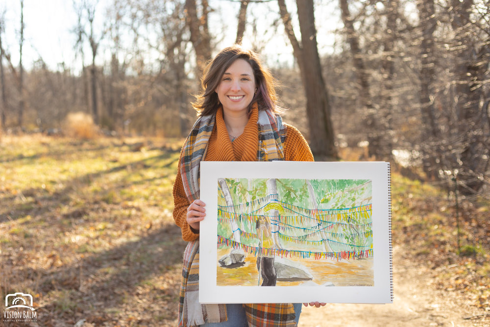 Professional fall portrait photography of Kayla Thornquist comic book artist and illustrator wearing an orange sweater in the park and holding her artwork photographed by Vision Balm in Charleston, SC.