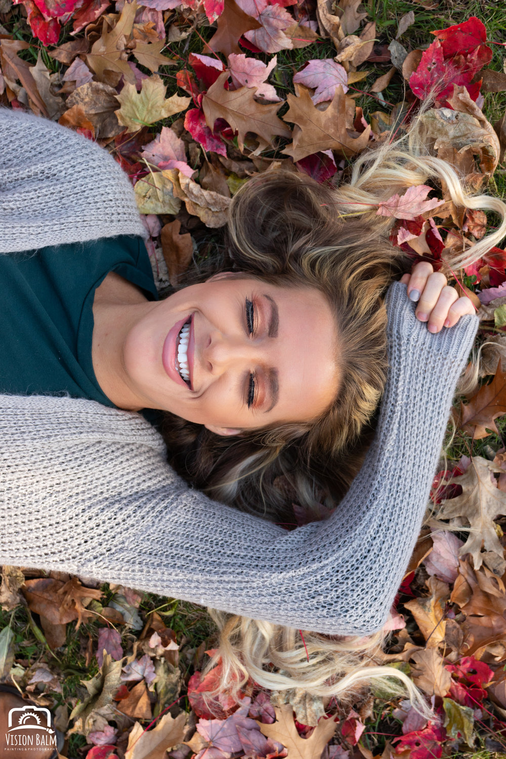 Professional fall portrait photography of model wearing a knit hat sitting in leaves photographed by Vision Balm in Charleston, SC.