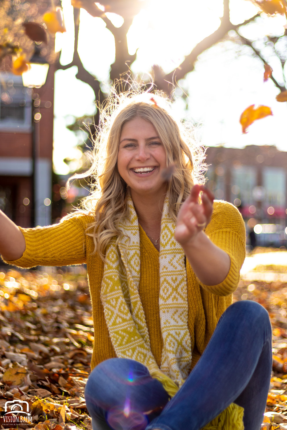 Professional fall portrait photography of model wearing a yellow sweater throwing leaves in downtown Newburyport, MA photographed by Vision Balm in Charleston, SC.