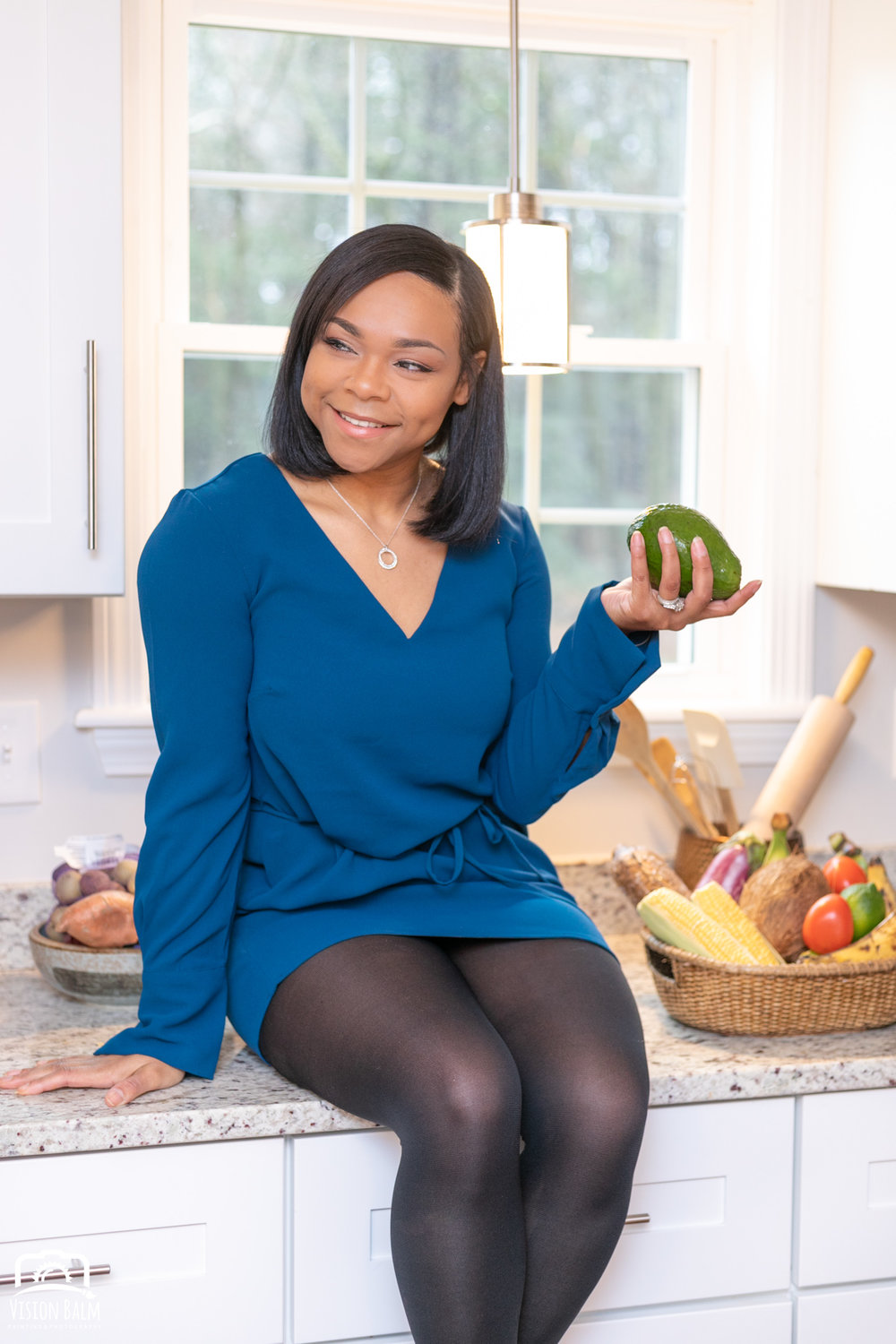 Professional portrait of a registered dietitian holding fruit in her kitchen sitting on the counter top and wearing a blue dress photographed by Vision Balm in Charleston, SC.