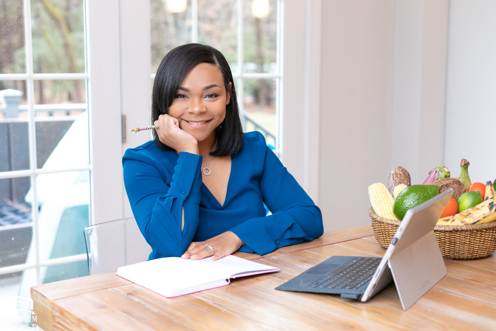 Professional lifestyle portrait of a registered dietitian working on her laptop and notepad on her kitchen table wearing a blue dress photographed by Vision Balm in Charleston, SC.