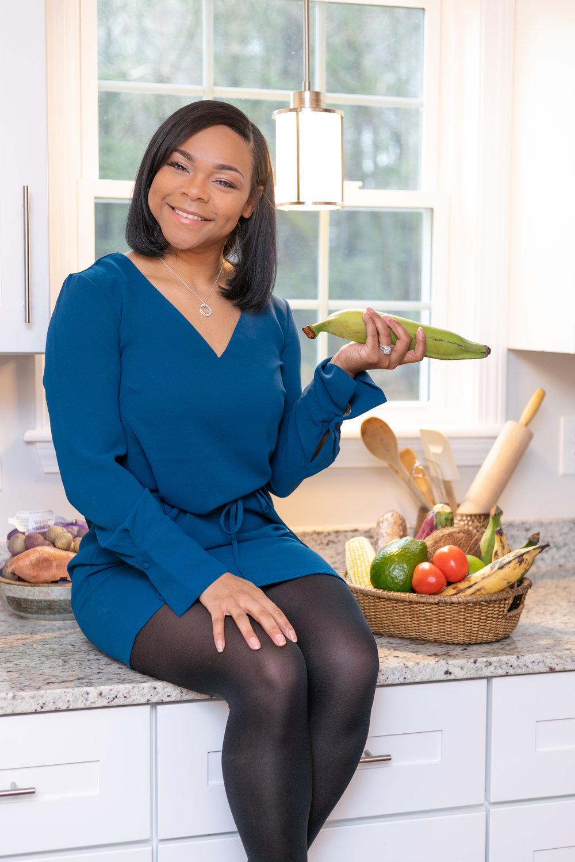 Portrait / headshot of Enjie M.K., aspiring RD, holding fruit in the kitchen, by Vision Balm in Charleston, SC