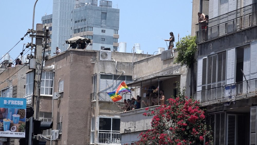 Dancing people on houses and roofs at the GayPride Tel Aviv 2018 track