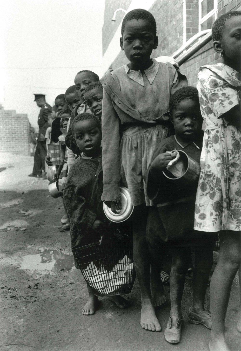 1962 – South African Children's feeding scheme, Orlando township, The scheme was a charity sponsored by wealthy white women.   Courtesy of the Estate of John Goldblatt