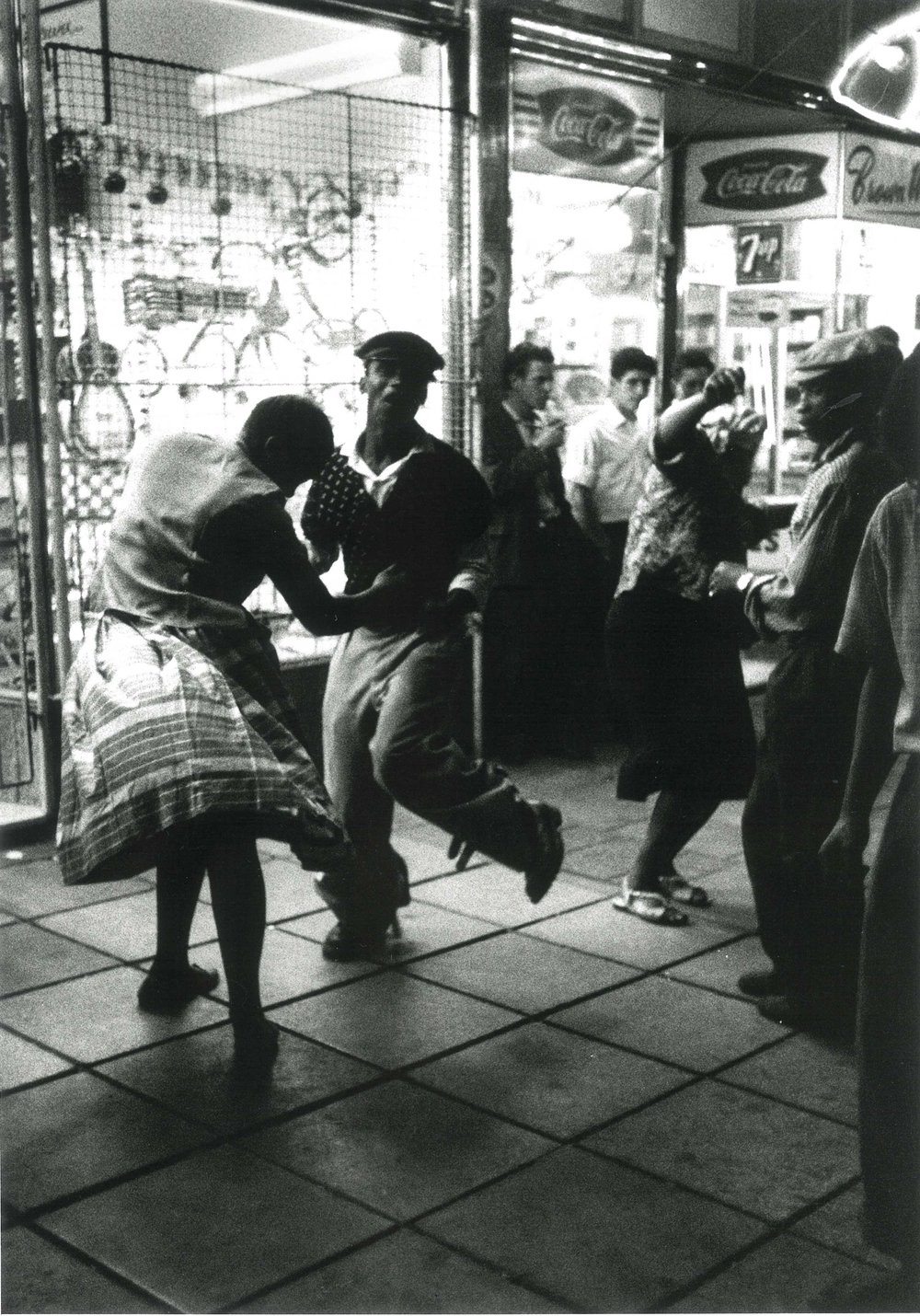 1960 – With no place to go for entertainment after work, black servants of white flats in Hilbrow, Johannesburg, dancing in the streets at night   Courtesy of the Estate of John Goldblatt
