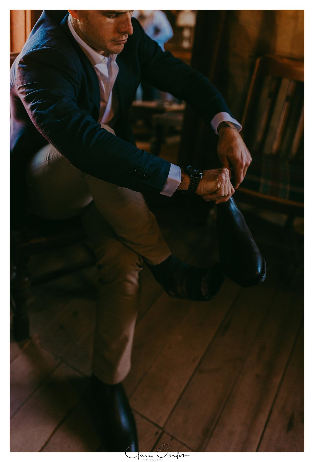 Groom-Getting-Ready-the-red-barn