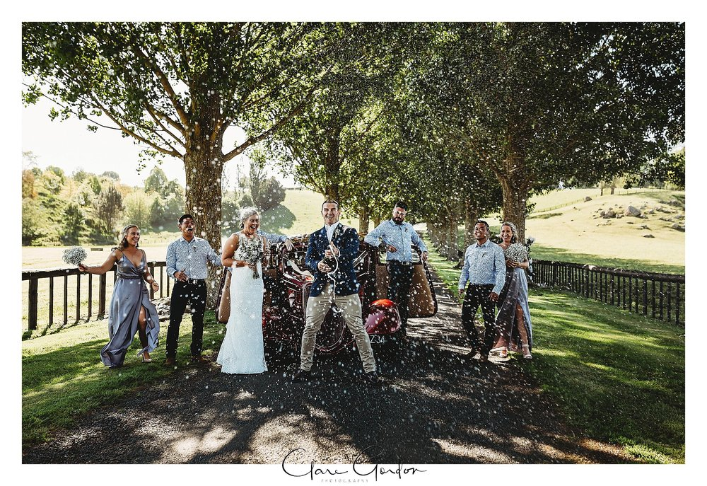 The-Red-Barn-Bridal-party-on-driveway-with-car-Champagne-pop