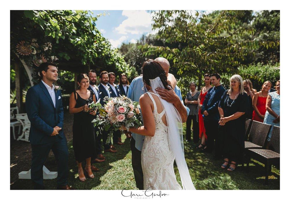 Bride-and-father-walking-down-aisle-The-boat-shed-lake-karapiro