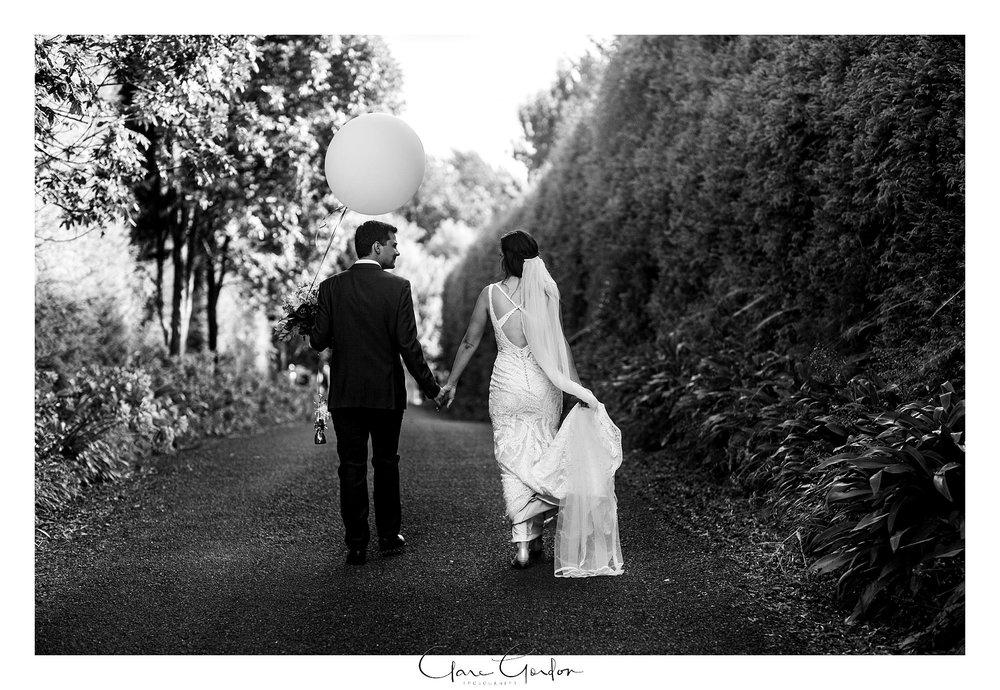 bride-and groom-walking-with balloon-the-boat-shed-lake-karapiro