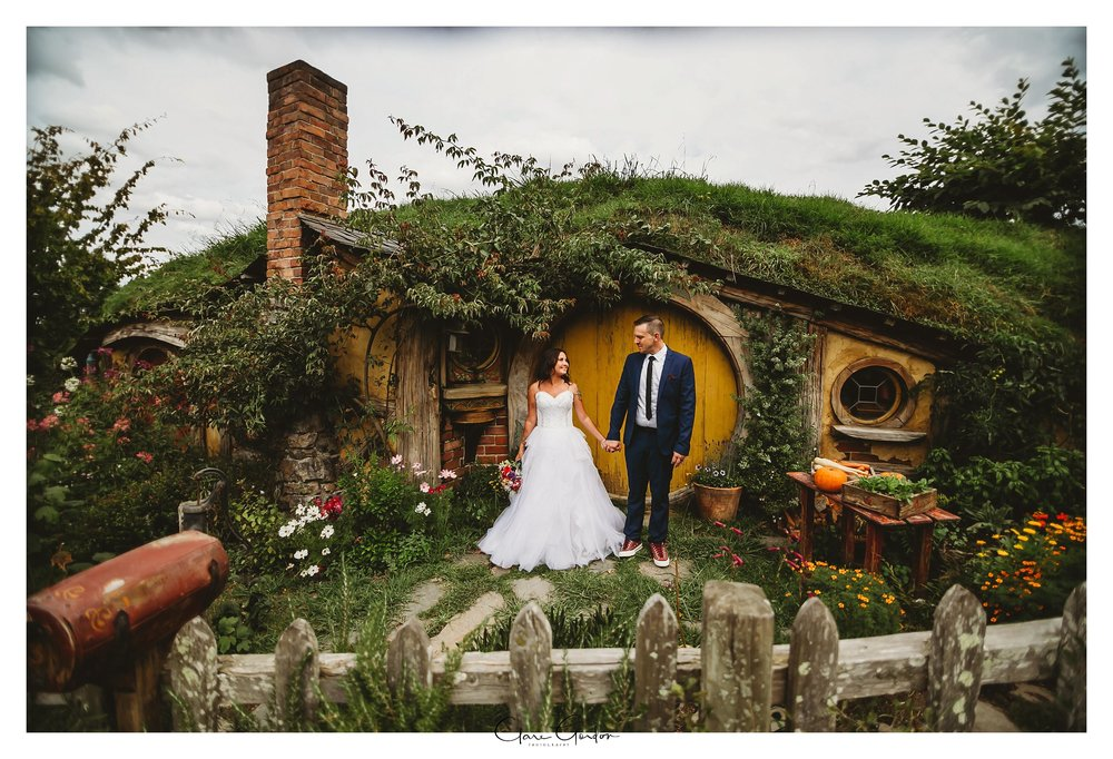 Hobbiton-wedding-photo-bride-and-groom-standing-in-front-of-hobbit-hole