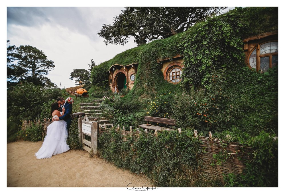 Bride-and-groom-kissing-in-front-of-Bilbo-Baggins-hobbit-hole