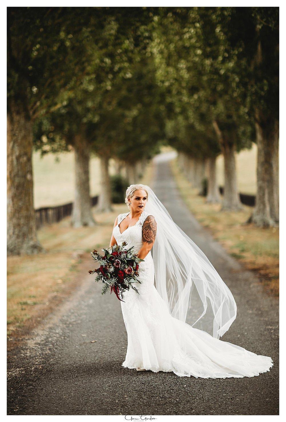 Bride-portrait-on-driveway-red-barn-waikato