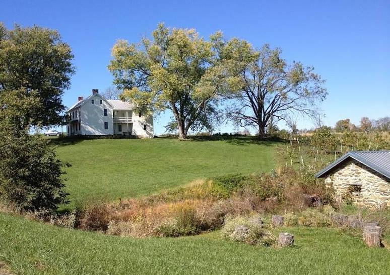 The house is surrounded by cornfields and other farms.