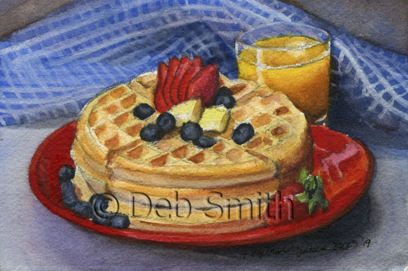 A perfect way to start the day, waffles, orange juice, blueberries, and strawberries.