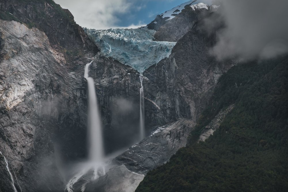 """ Why we like it : Chile is home to some of planet earth's most breathtaking natural wonders and panoramic landscapes, and Javi's capture of this glacier mid-flow showcases them perfectly. The moody, stormy clouds and dark, thick forests that frame the shot give it an extra flourish of drama, and feel almost as though they are creeping into the camera lens itself."" -    Source      — Emily Frost, Lonely Planet"