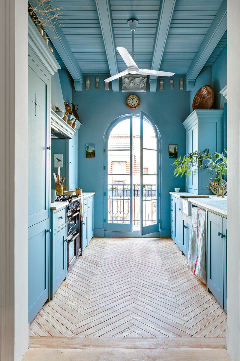 Not just blue cabinets but also blue walls ánd ceiling certainly make this kitchen stand out. The beautiful wooden floor gives this kitchen some warmth and calmness | photo by  Ricardo Labougle
