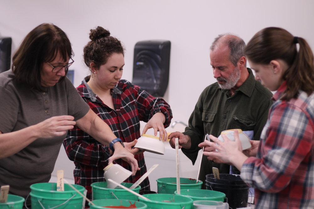 pottery students dipping glaze.JPG