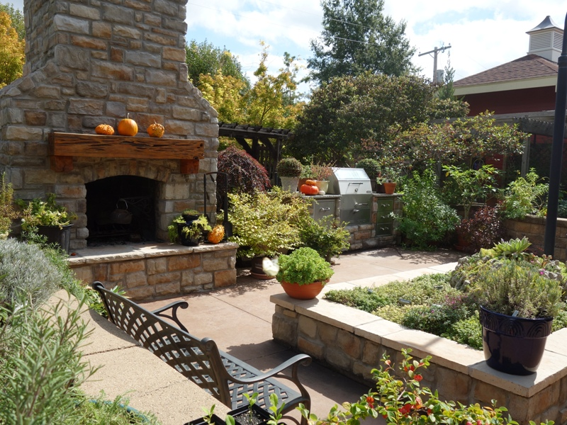 Herbs such as basil, soft Lamb's Ear, and echinacea are planted along each border and center of the Herb Garden which includes an outdoor fireplace and kitchen.