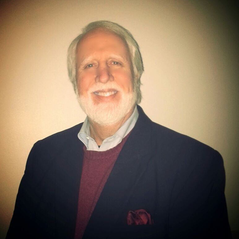 Joe James with a beard and hair, wearing a collared shirt and blazer.
