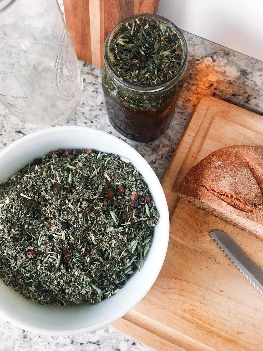Mixing a nettle, oatstraw, raspberry leaf, rosehip, hawthorn berry, & lemon balm infusion