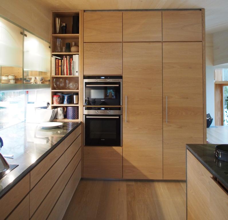 Kjøkken - Ett eksempel på kjøkken i enebolig, tegnet av Knut Hjeltnes. Fronter av hvitpigmentert eikefinèr og benkeplate i polert Oppdal skifer.