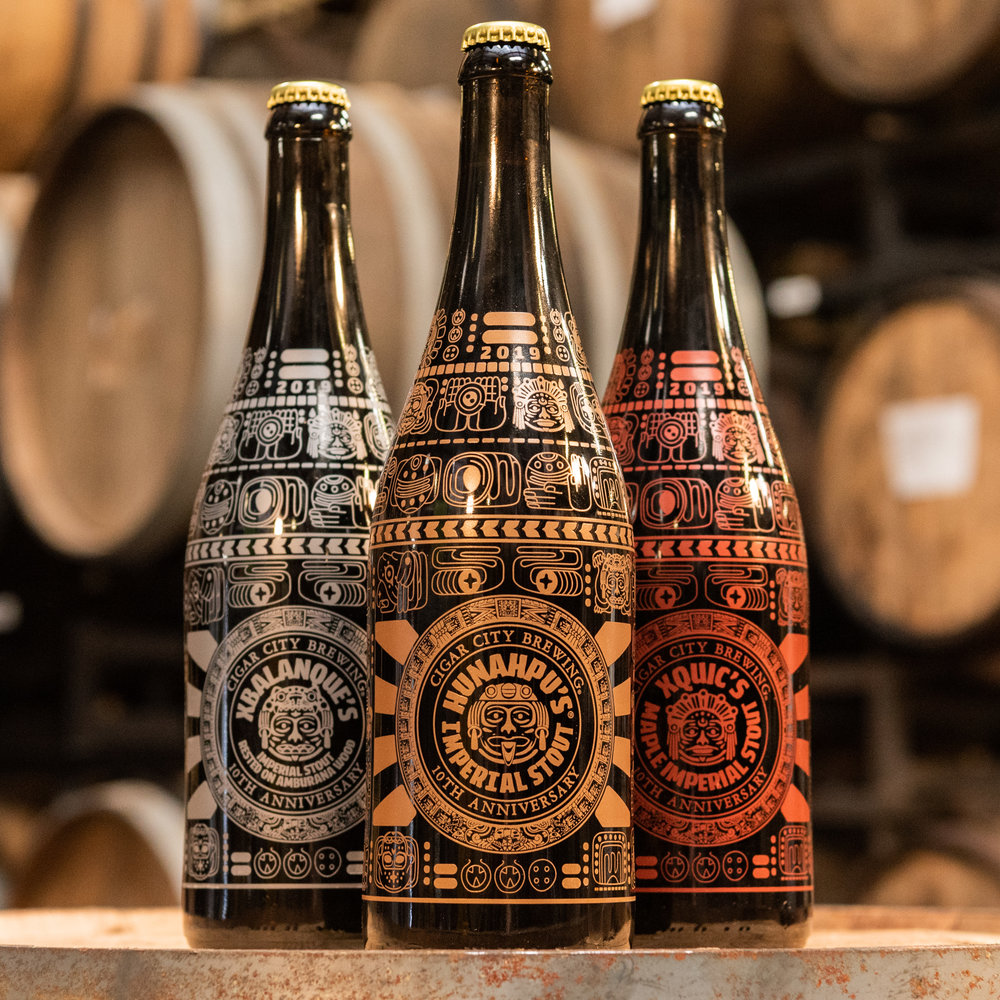 2019's bottles: Hunahpu's® Imperial Stout (gold), Xbalanque (silver), and Xquic (red)