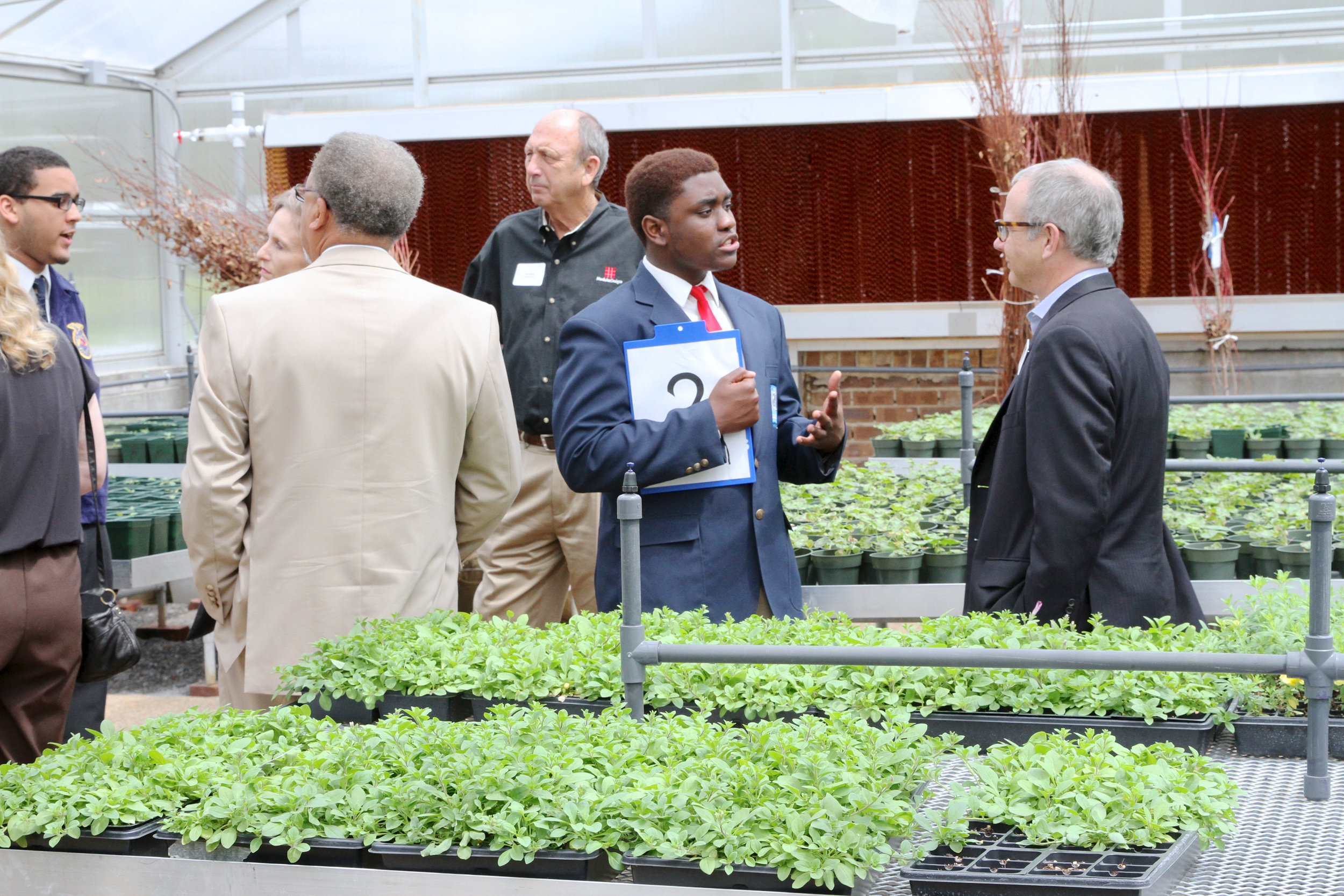 VIPs tour the Academy of Alternative Energy, Sustainability, and Logistics greenhouse.