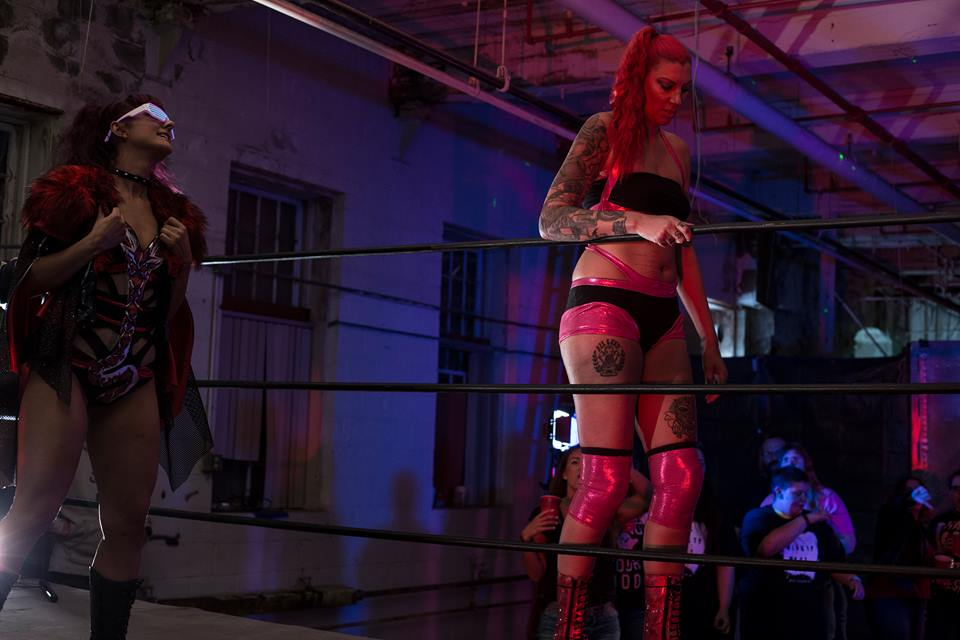 Her opponent Lacey Tormada enters in a contrasting pink and black ensemble with matching knee pads. Actress Lizzie Havoc