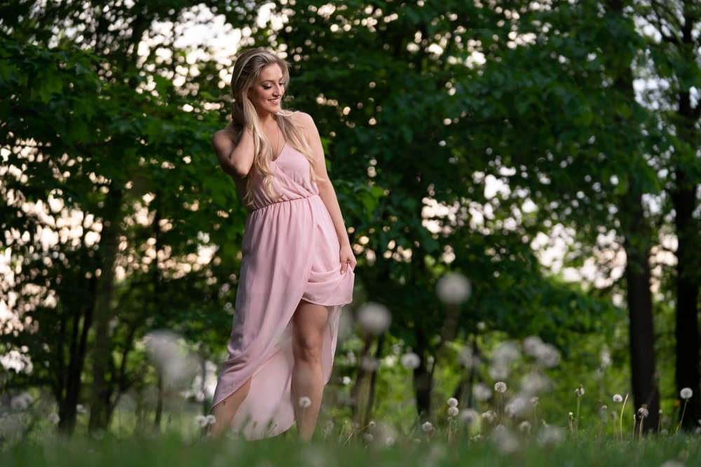 Blonde woman in pink dress standing in woods