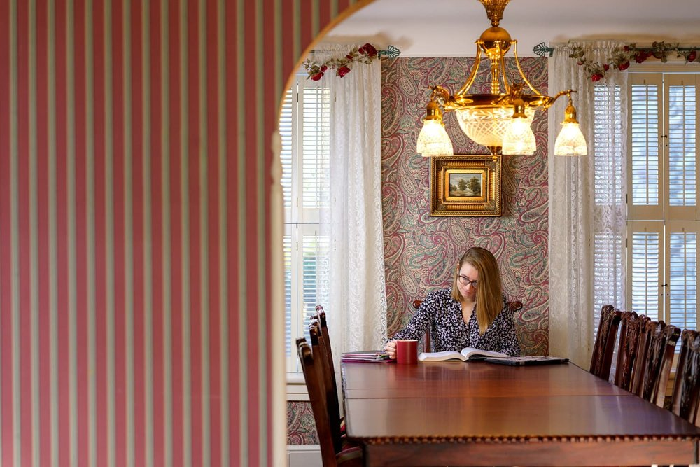 student with coffee at dining room table