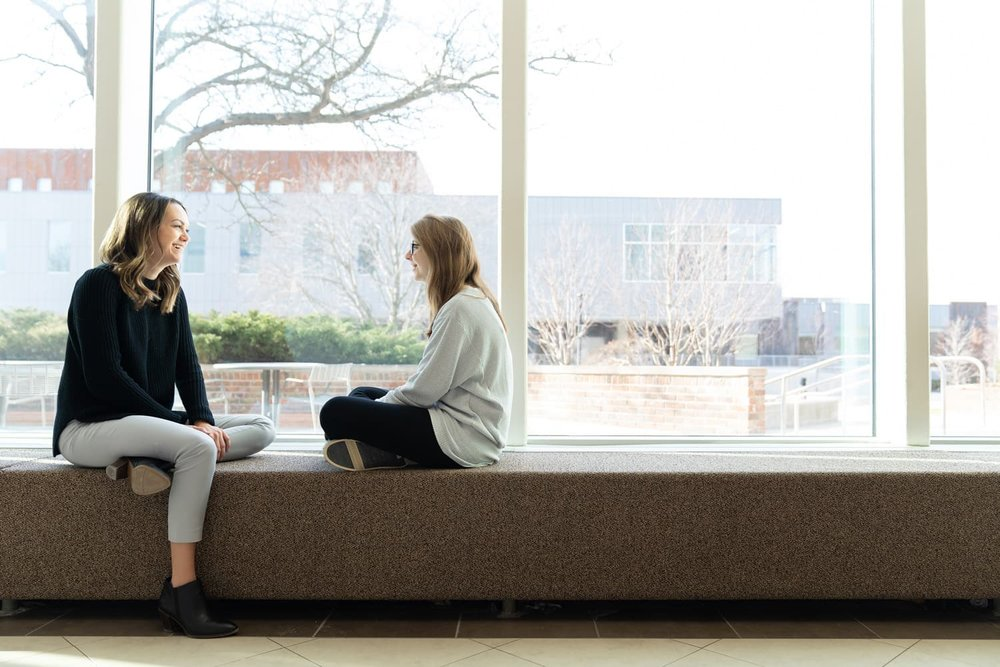 student and advisor sitting and talking near windows