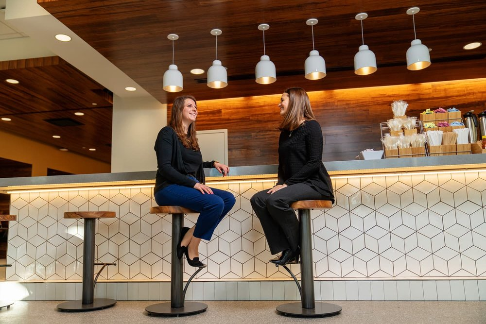 Two people talking at cafe counter