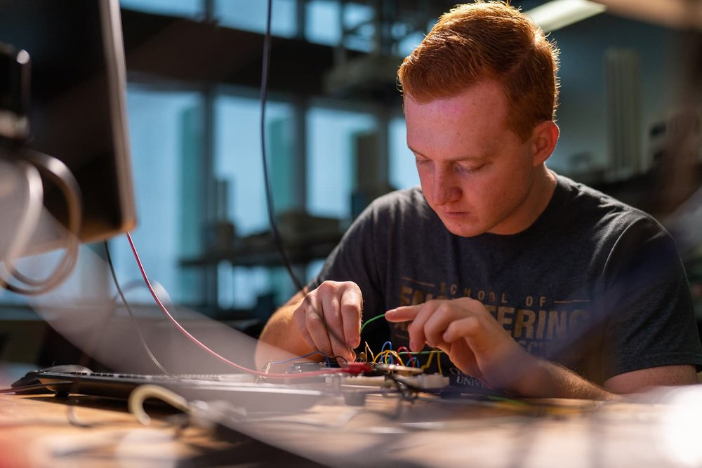 Engineering student tinkering with circuit board