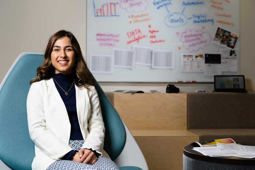 student in white coat sitting in blue chair in front of whiteboard