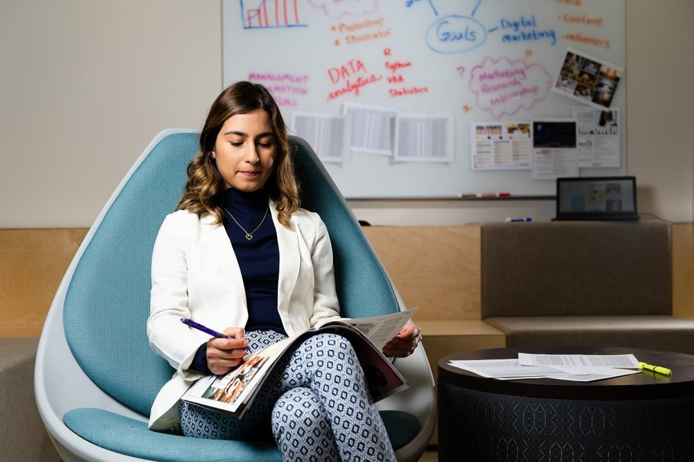 student in white coat sitting in blue chair writing