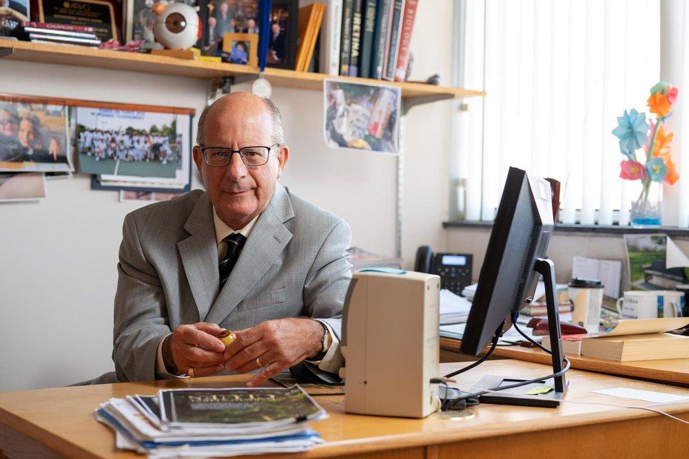 Doctor holding model eye at desk