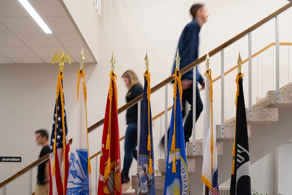 students walking on stairs, armed forces flags in foreground
