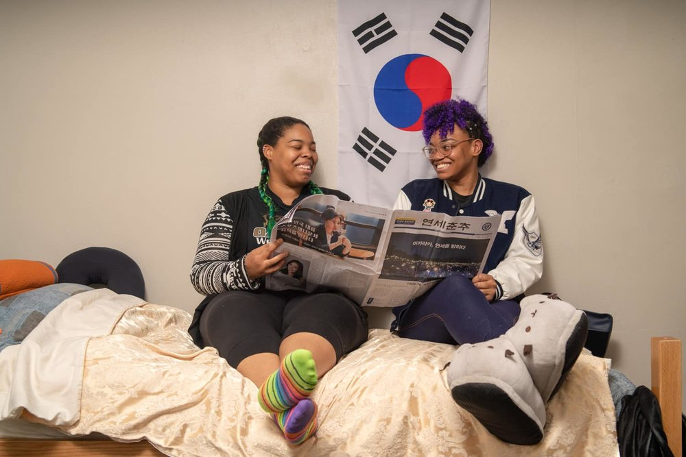 two students laughing while reading the newspaper