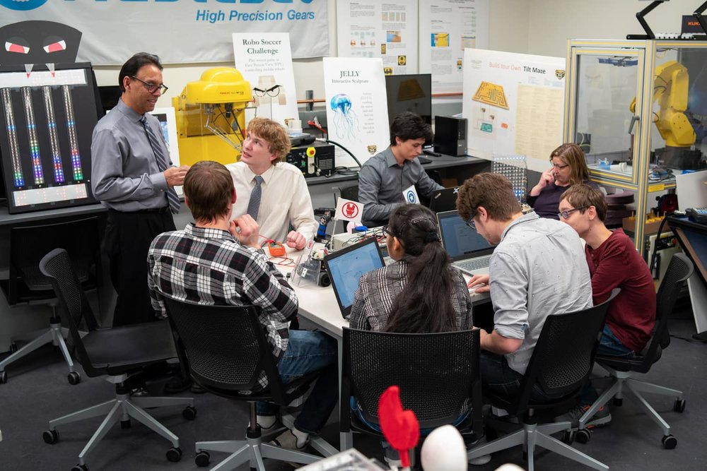 Professor and Oakland University students around a table working on various engineering projects.