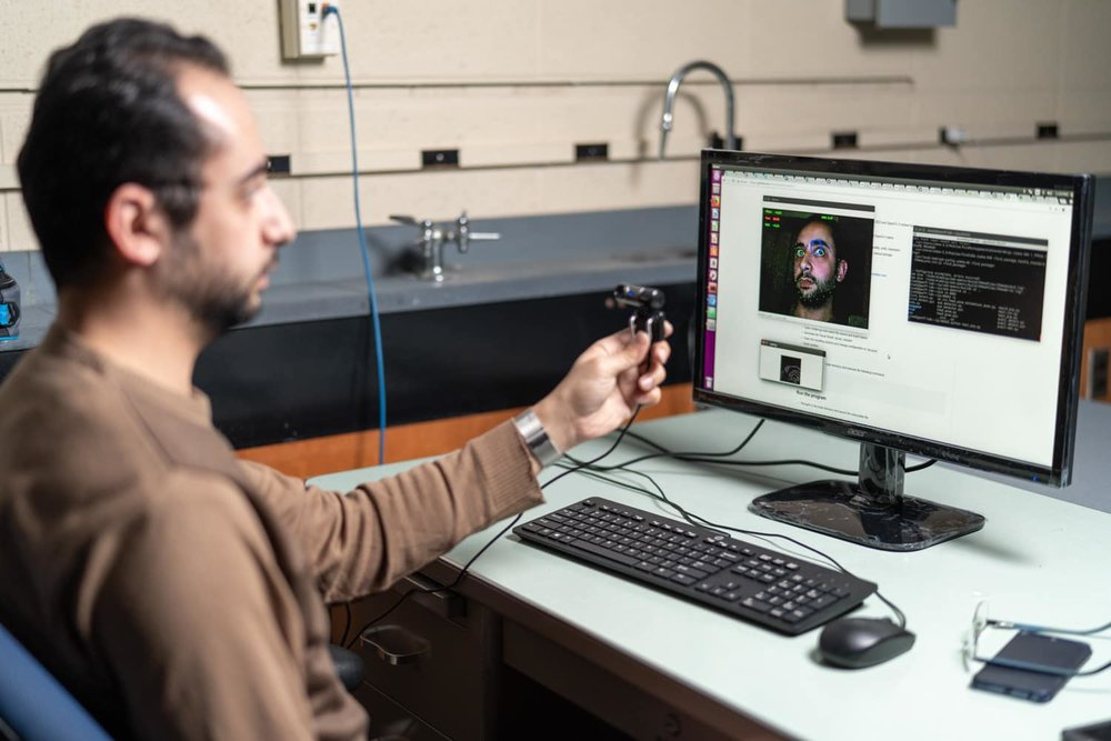 Student holding camera in front of computer with face detection software on screen