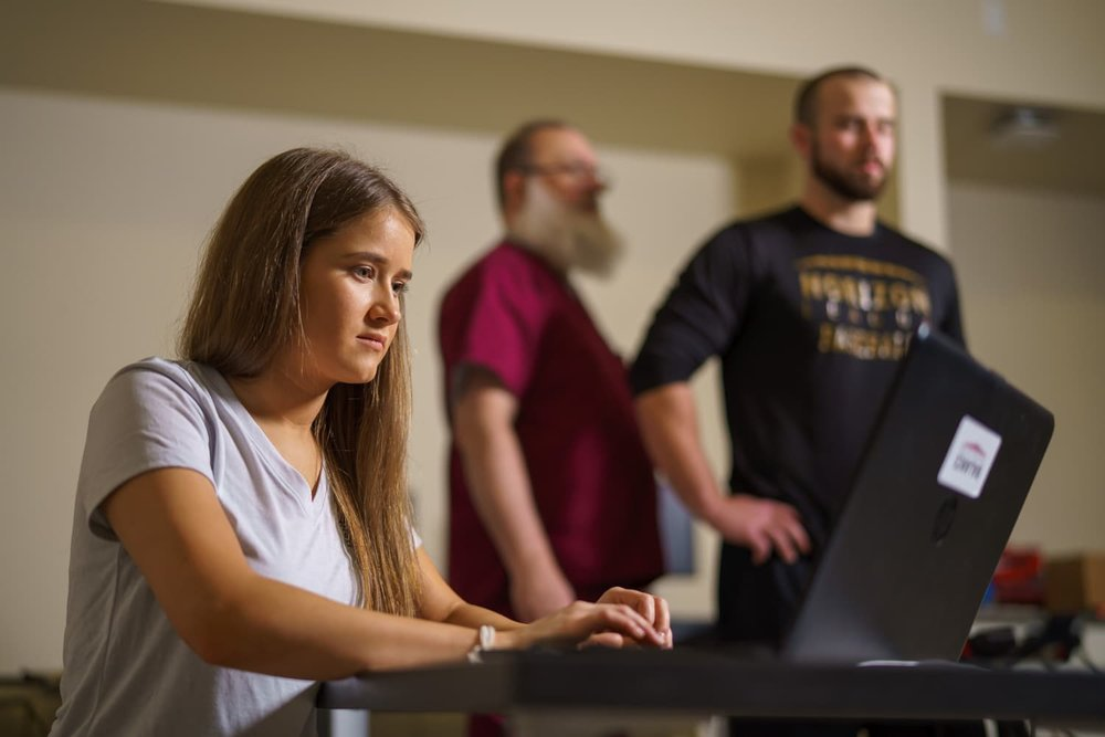 student on computer with athlete in background