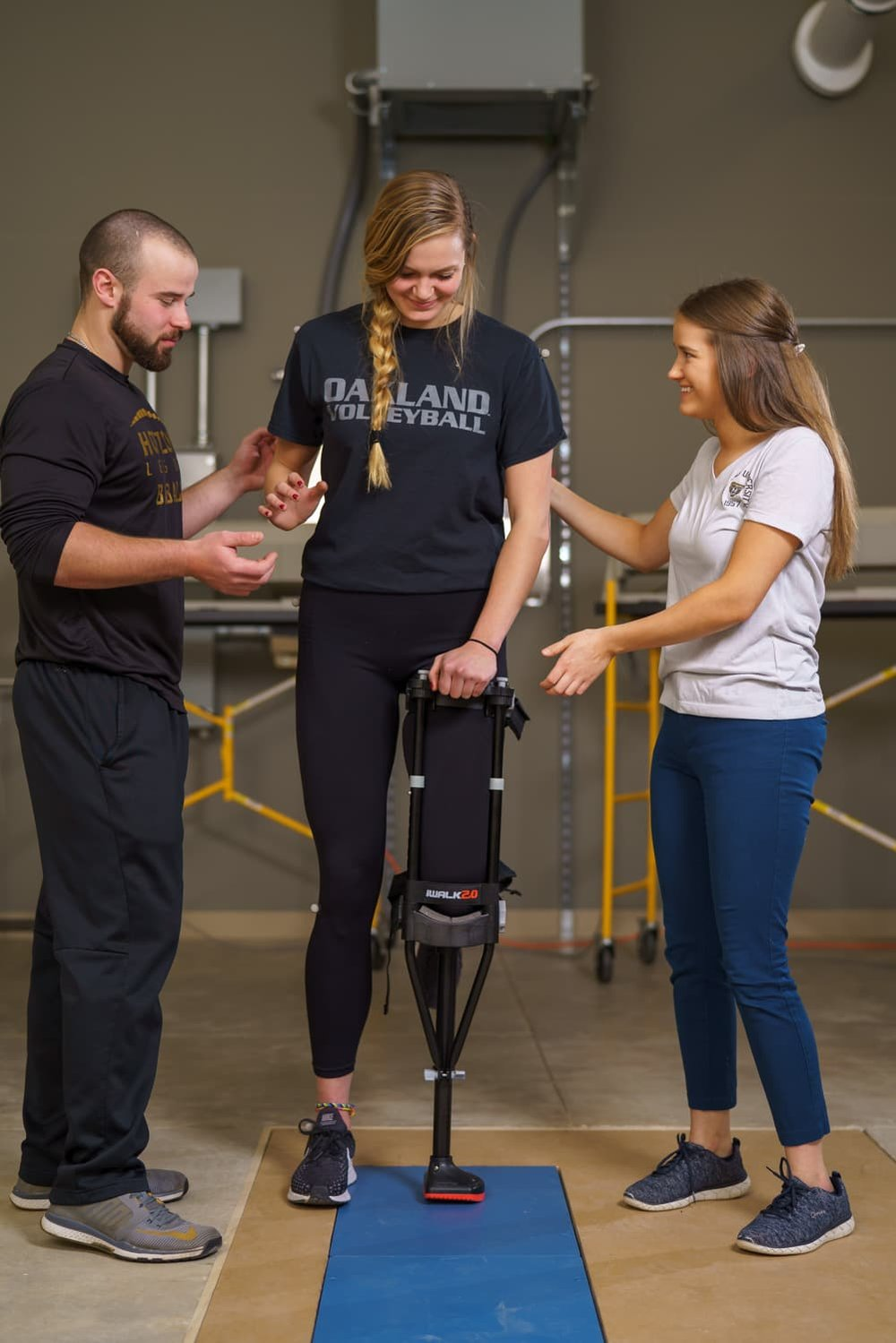 students assisting athlete while monitoring balance