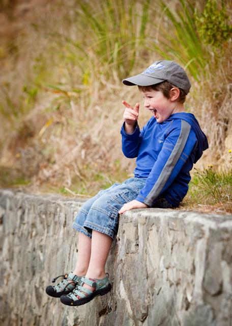 Pre-school boy sitting on a wall