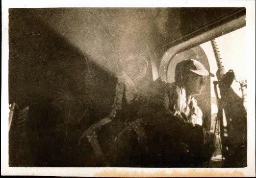 A WW2 photo of a man inside an aircraft near a gun.