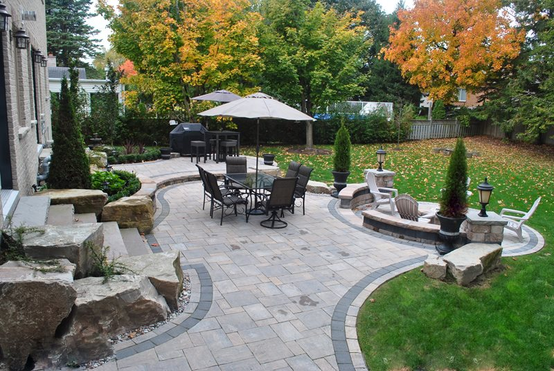 An inviting paver patio provides plenty of room for daily activities while special events can easily spill into the well-kept lawn.