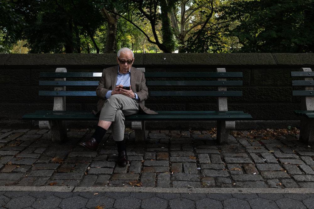 DeniseLaurinaitisNewYorkCityStreetPhotographerOldManParkBenchPhone.jpg