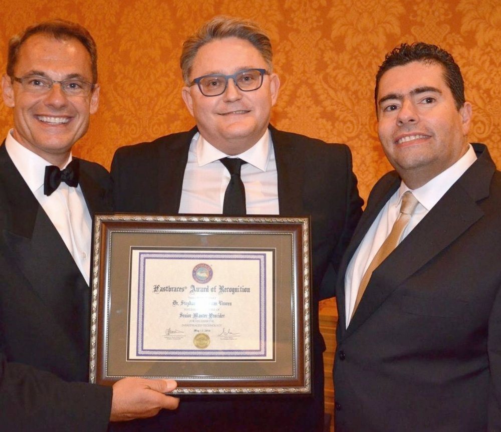 - Tony Viazis (left), the inventor of FASTBRACES®, presenting Stephan van Vuuren (middle) with the Senior Master Provider award in Dallas in 2016. On the right is Evangelos Viazis, who has done some magical work with FASTBRACES® in his practices in Athens.